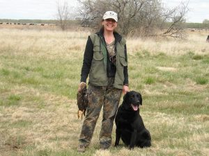 Happy owner with her black Lab after a successful day at an HRC hunt test in CO