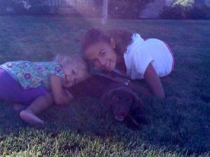 Two girls with their favorite chocolate Lab puppy